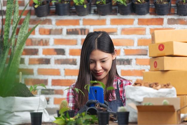 植物をオンラインで販売する。携帯電話で植物の写真を撮る女性