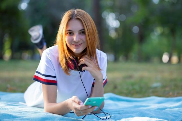 公園で屋外のsellphoneを使用して赤い髪のかなり笑顔の10代の少女。