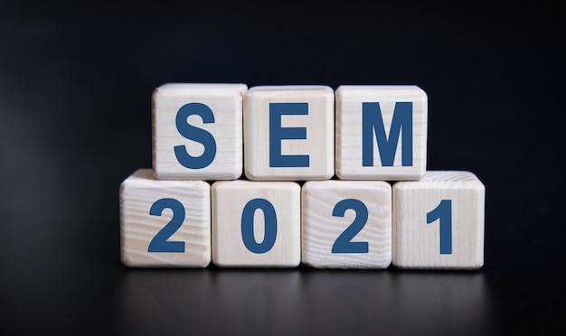 Текст sem 2021 на деревянных кубиках на черном фоне с отражением.