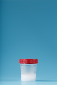 Semen in a test container with a red lid on blue