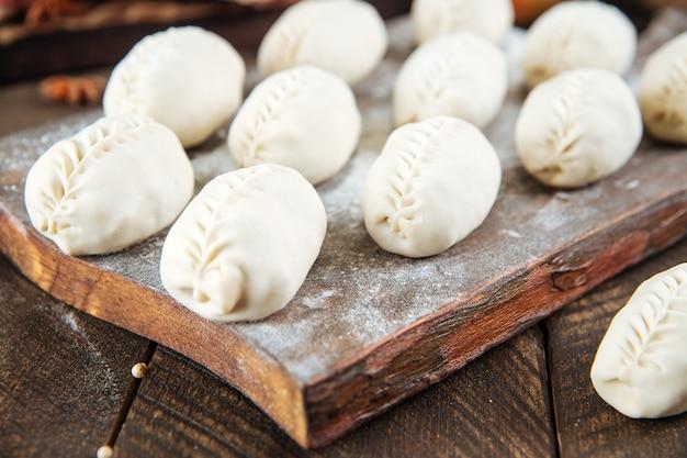 Полуфабрикаты манти пельмени на деревянной доске