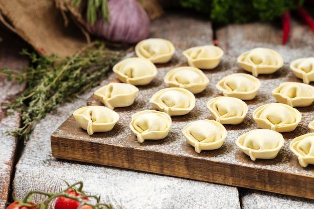 Semi-finished pelmeni dumplings on wooden board