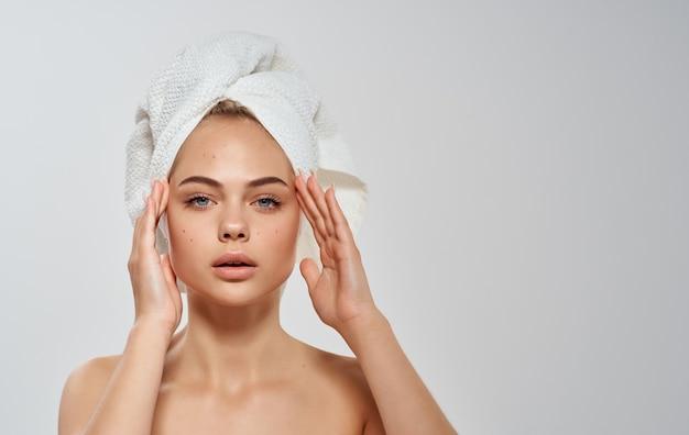 Полуобнаженная женщина поправляет полотенце на голове, чистая кожа, волосы модель