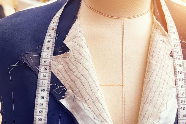 首に巻尺が付いたマネキンのセミレディジャケット。カスタムメイドのジャケットの工程でのスーツの仕立て。テーラーワークショップでのオーダーメイドのスーツテーラリング。オーダーメードのスーツジャケットに取り組んでいます