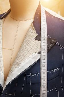 首に巻尺が付いたマネキンのセミレディジャケット。カスタムメイドのジャケットの仕立てのスーツ。テーラーワークショップでのオーダーメイドのスーツテーラリング。オーダーメードのスーツジャケットに取り組んでいます