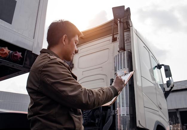 Азиатский водитель грузовика держа доску сзажимом для бумаги проверяя контрольный список обслуживания автомобиля безопасности semi semi грузовика