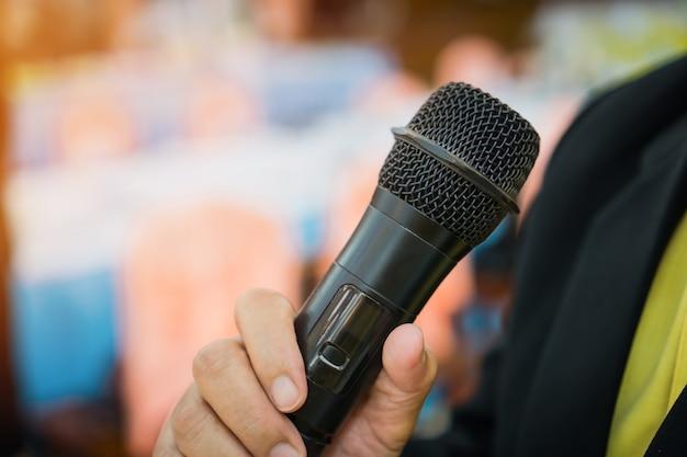 Концепция конференции: руки деловых людей, держащих микрофоны для речи
