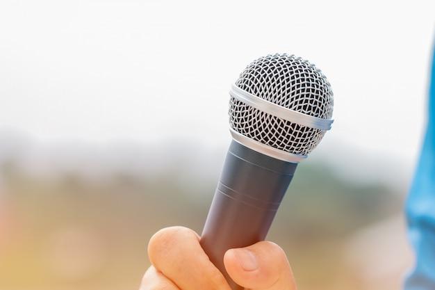 Концепция конференции семинара: руки бизнесменов держат микрофоны для выступления или выступают в аудитории, разговаривают на лекции перед аудиторией университета