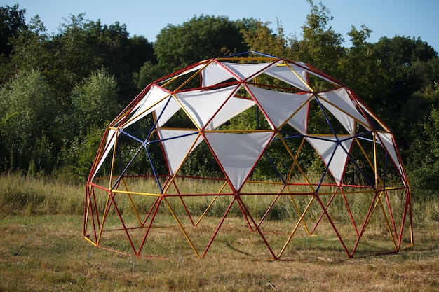 Semispherical structure with fabric awnings for relaxing in a meadow near the forest