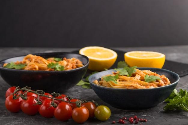 黒いコンクリートの表面にトマトのペストソース、オレンジ、ハーブを添えたセモリナパスタ。側面図、セレクティブフォーカス、コピースペース。