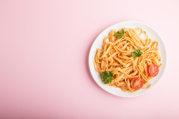 セモリナ粉のパスタ、トマトのペストソース、オレンジ、ピンクのパステル調の背景にハーブ。トップビュー、コピースペース。