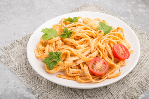 Semolina pasta with tomato pesto sauce, orange and herbs on a gray concrete background. side view.