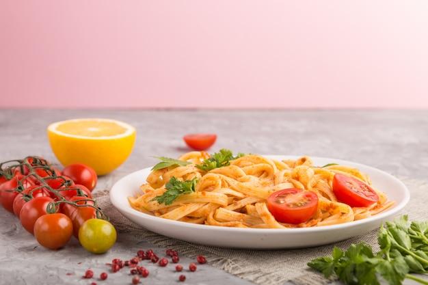 Semolina pasta with tomato pesto sauce, orange and herbs. side view