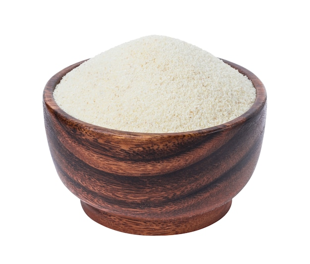 Semolina in wooden bowl isolated on white
