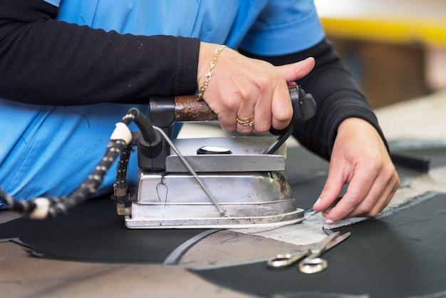 Швея гладит ткань. швея утюги фабричные в швейной мастерской.