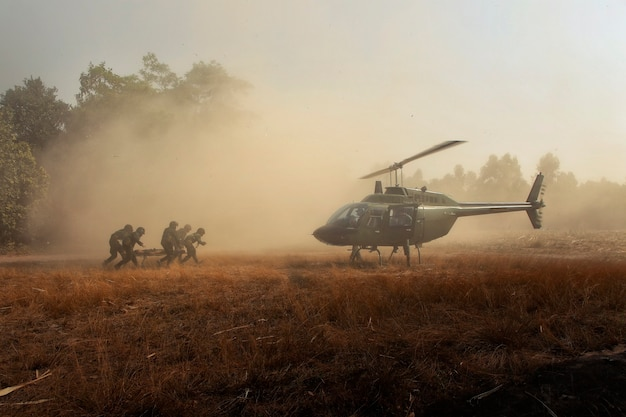 Sending injured soldiers back by helicopter. combat soldiers carrying a wounded friend