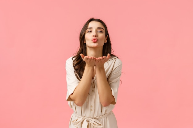 Sending love and care. charming cute and tender european brunette with curly hair, wearing spring dress, leaning with hands near folded lips, blowing air kiss with love, standing pink