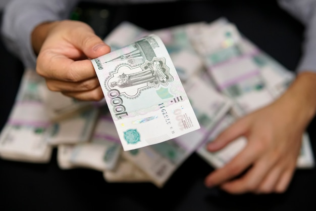 Sending money from one hand to another. man pay money for trading,buy something exchanging or sending fraudulent money, corruption. bill 1000 rubles in one hand a million rubles in the other