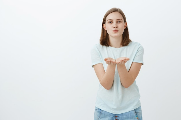 Sending sweet kiss by air. portrait of charming carefree cute woman in trendy t-shirt bending towards with palms opened near chest folding lips to blow mwah smiling shy