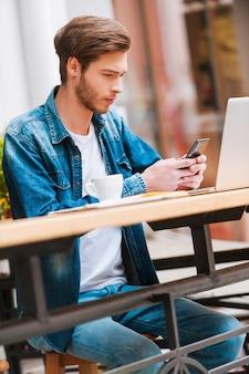 緊急メッセージを送信します。歩道のカフェに座って携帯電話を持っている集中若い男