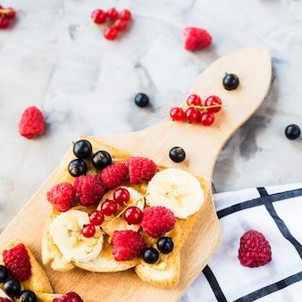 ピーナッツバター、バナナ、ラズベリーとスグリの木の板にsendvci