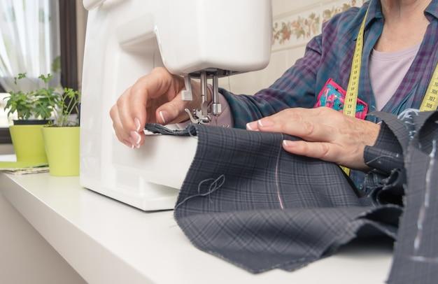 Senion seamstress woman working on sewing machine