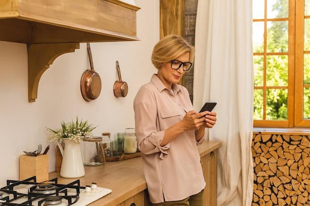 Старшая женщина 50 лет с помощью приложений, заказывающих еду на смартфоне, сидя на кухне у себя дома. пожилая пожилая дама, держащая текстовые сообщения мобильного телефона.