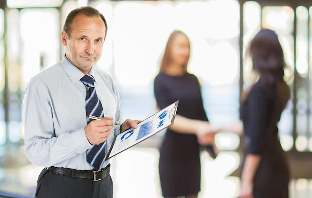 Старший бухгалтер с финансовым графиком на фоне офиса.