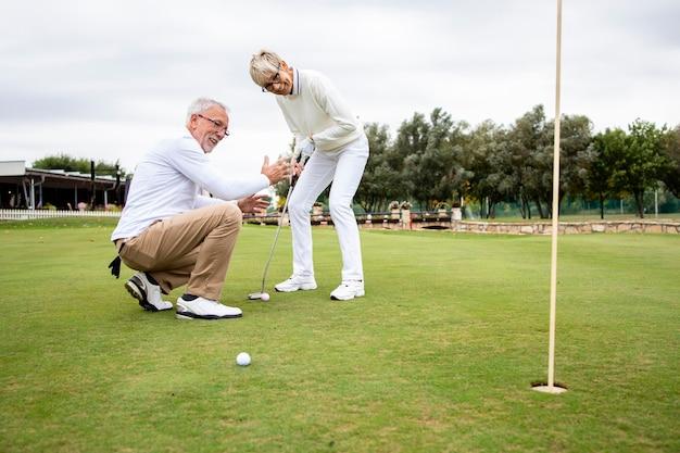 Старшие активные люди веселятся на поле для гольфа и проводят свободное время на свежем воздухе.