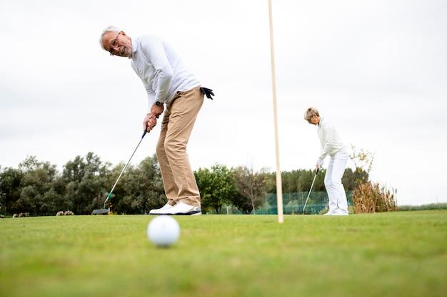 Старшие активные люди играют в золото на поле для гольфа и проводят свободное время на свежем воздухе.