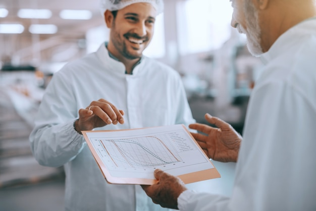 Senior adult caucasian inspector holding folder with chart of quality of product and talking to employee. both having sterile uniforms and hairnets on. food plant interior.