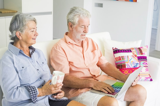 Senior adult caucasian people couple at home using technology with internet connected laptop with coloured keyboard