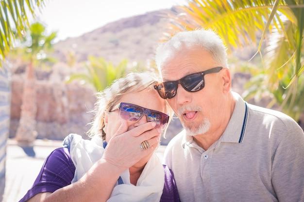 一緒に楽しんでいる年配の大人の白人の人々-休暇中の老夫婦のために笑っている素敵な顔。手のひらと日光と彼らはサングラスをかけています。素敵で面白い人生のコンセプト。