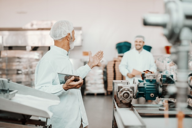 Senior adult caucasian supervisor talking to his younger colleague about quality of food. man holding tablet. both are dressed in white uniforms and having hairnets. food plant interior.