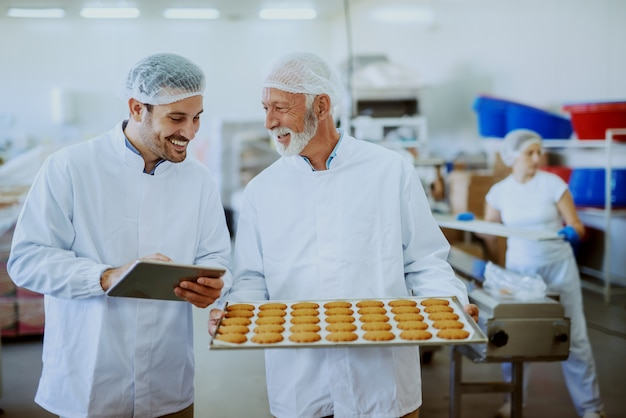 Senior adult employee in sterile white uniform standing with tray with cookies in food plant. next to him standing supervisor, holding tablet and checking quality of food.