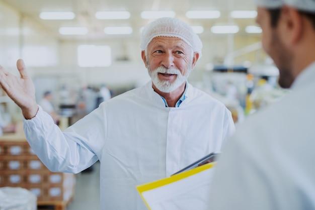 食品の品質について従業員と話しているシニア大人のマネージャー。どちらも無菌の制服に身を包んだ。食品工場のインテリア。