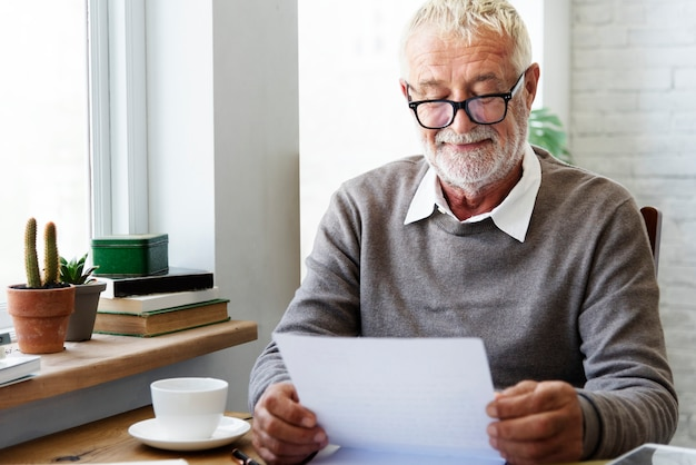 Senior adult reading letter postcard concept