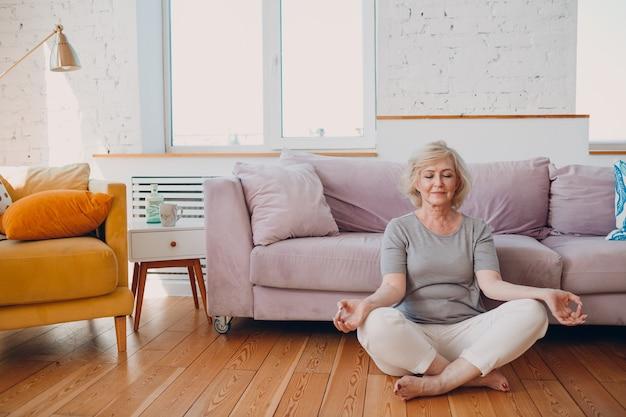 집 거실에서 요가를 연습하는 수석 성인 웃는 여자. 로터스 포즈에 앉아 소파 근처에서 선을 명상하는 노인 편안한 여성
