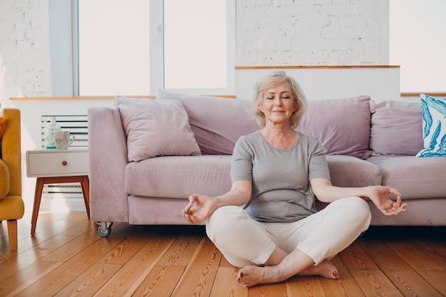 自宅の居間でヨガを練習している年配の大人の笑顔の女性。蓮華座に座り、禅のように瞑想する年配のリラックスした女性。