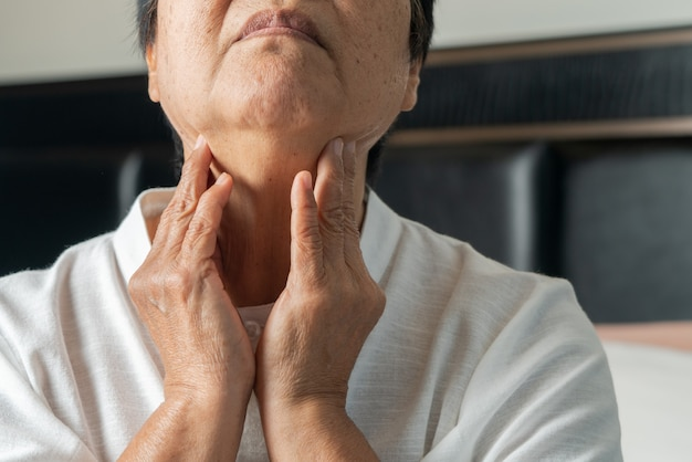 Senior adult women touching the neck feeling unwell coughing with sore throat pain.