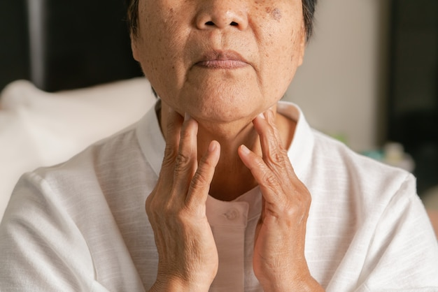 목에 통증이있는 기침을 느끼는 노인 여성 건강 관리 및 의학 개념