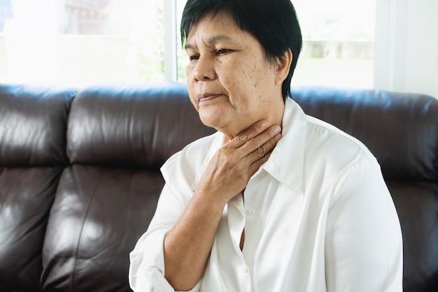 목을 만지는 노인 여성은 인후통으로 기침을 하는 기분이 좋지 않습니다. 건강 관리 및 의학 개념