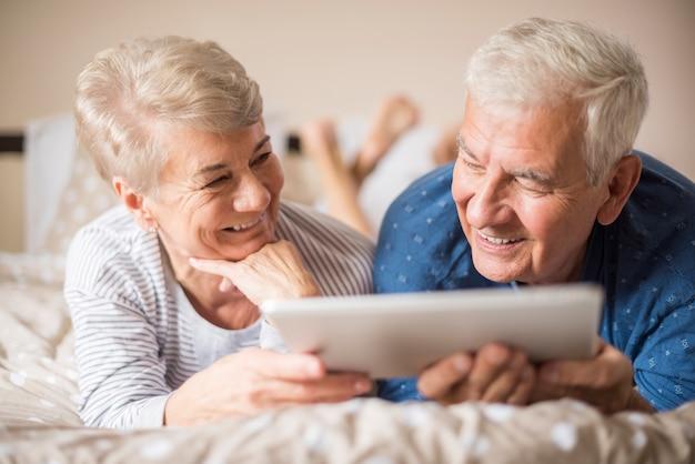 一緒にインターネットを閲覧する高齢者