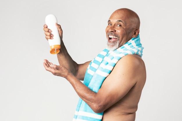 선 스크린 로션 병을 들고 수석 아프리카계 미국인 남자