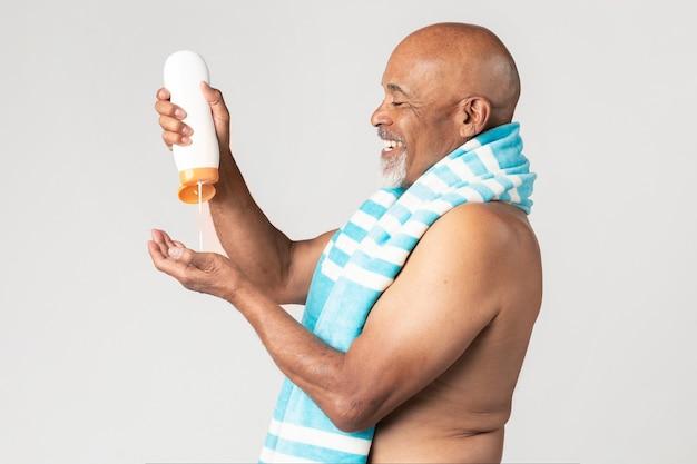 Старший афро-американский мужчина держит бутылку солнцезащитного лосьона