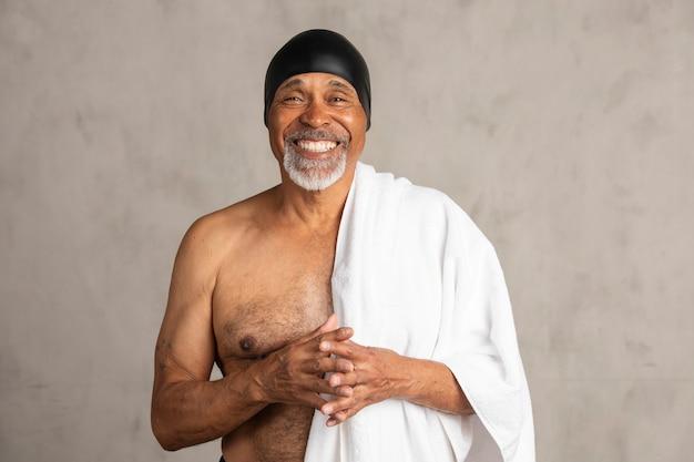 흰색 목욕 수건을 든 수석 아프리카계 미국인 남자
