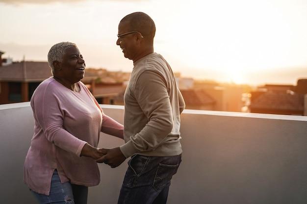 夏の日没で屋外で踊るシニアアフリカのカップル-女性の顔に焦点を当てる