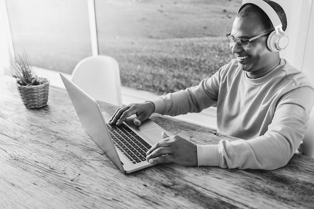 집에서 헤드폰을 착용하는 동안 랩톱 컴퓨터를 사용하는 수석 아프리카 남자