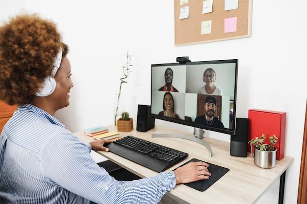 Старшая африканская женщина разговаривает по видеосвязи со своими коллегами с помощью компьютерного приложения - фокус на правой руке