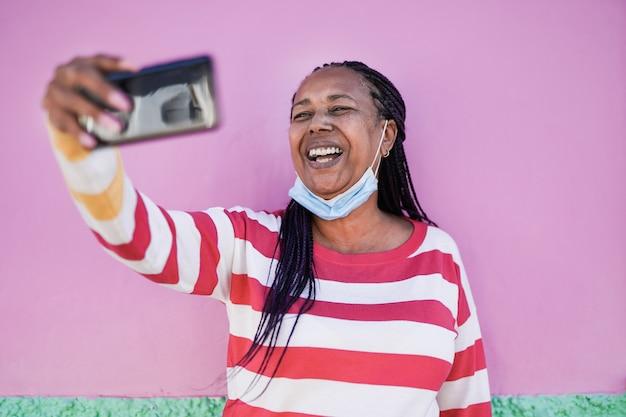あごの下に安全フェイスマスクを着用しながら市内のスマートフォンでビデオ通話で話している年配のアフリカの女性-自分撮りをするために携帯電話を使用している年配の黒人女性